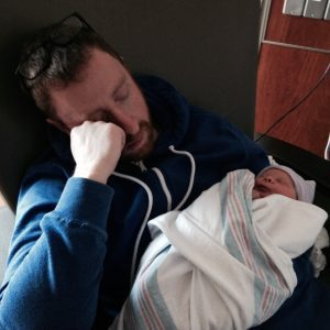 Sleepy new daddy Brian with our baby girl.