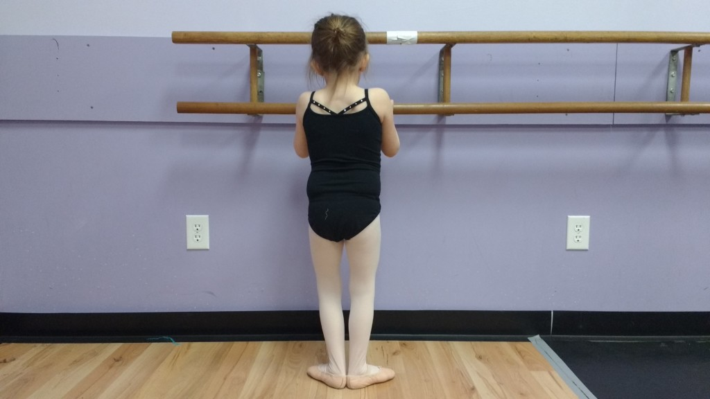 Am I Over-Scheduling my Child? Young child in black leotard, pink tights, and pink ballet slippers at barre in ballet class.