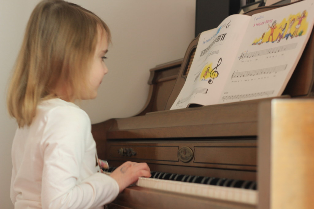Am I Over-Scheduling my Child? Young girl, age five, playing piano.