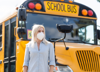 Woman in mask standing in front of school bus